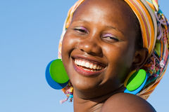 Beautiful african woman with scarf. Beautiful african woman laughing and having fun wearing a colorful scarf on blue sky background Royalty Free Stock Image