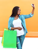 Beautiful african woman with shopping bags makes self-portrait on smartphone Royalty Free Stock Photo