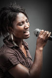 Beautiful African woman singing with the microphone royalty free stock photos