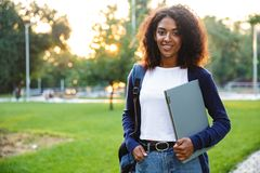 Beautiful african woman student walking in the park holding laptop computer. Image of young beautiful african woman student walking in the park holding laptop royalty free stock image