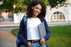 Beautiful african woman student walking in the park holding laptop computer. Image of young beautiful african woman student walking in the park holding laptop royalty free stock photos