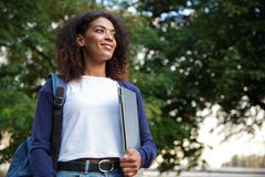 Beautiful african woman student walking in the park holding laptop computer. Image of young beautiful african woman student walking in the park holding laptop stock photography