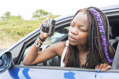 Beautiful african woman takes pictures from the car windows. Stock Photos