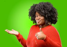 Beautiful african woman with curly hair isolated over green background. Beautiful african woman thumb up holding something in his empty hand and making ok Royalty Free Stock Image