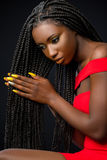 Beautiful african woman touching long braided hair. Close up studio portrait of sensual young african woman caressing long braided hair Stock Photography