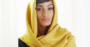 Beautiful African woman wearing gold head scarf in bright room Stock Photography