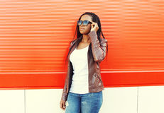 Beautiful african woman wearing a leather jacket and sunglasses Stock Photography
