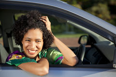 Beautiful African women leaning out of her car. Beautiful happy African woman leaning out of her car Stock Image