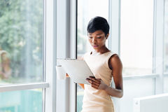 Beautiful african young businesswoman holding clipboard and reading in office Stock Photos