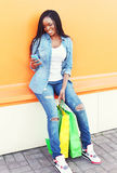 Beautiful african young woman with shopping bags using smartphone. In city over colorful orange background Stock Image