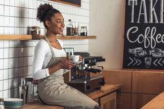 Afro American barista. Beautiful Afro American barista in apron is holding a cup of coffee, looking away and smiling while sitting on the counter near a coffee stock photos