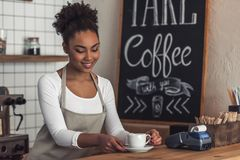 Afro American barista. Beautiful Afro American barista in apron is holding a cup and smiling while standing at bar counter royalty free stock photo