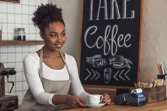 Afro American barista. Beautiful Afro American barista in apron is holding a cup and smiling while standing at bar counter stock photography