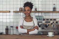 Afro American barista. Beautiful Afro American barista in apron is looking at camera and smiling while standing with the crossed arms at the bar counter stock photography