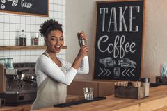 Afro American barista. Beautiful Afro American barista in apron is preparing a cocktail in shaker and smiling while standing at bar counter royalty free stock photos