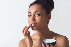 Beautiful Afro-American girl. Is applying cream, looking at camera and smiling, isolated on white Stock Photo
