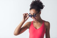 Beautiful Afro-American girl. In bright pink swimsuit and sun glasses is looking at camera and smiling, isolated on white Stock Photos
