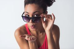Beautiful Afro-American girl. In bright pink swimsuit and sun glasses is sending air kiss at camera, isolated on white Royalty Free Stock Image