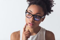 Beautiful Afro-American girl. In eyeglasses is looking away and thinking, isolated on white Royalty Free Stock Images
