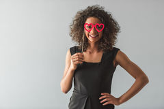 Beautiful Afro American girl. In black cocktail dress is holding a paper glasses, looking at camera and smiling, on gray background Royalty Free Stock Images
