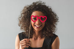 Beautiful Afro American girl. In black cocktail dress is holding a paper glasses, looking at camera and smiling, on gray background Royalty Free Stock Image