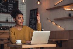Afro American girl in cafe. Beautiful Afro American girl in casual clothes is calling a waiter while sitting with a laptop in the cafe royalty free stock photo