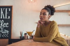 Afro American girl in cafe. Beautiful Afro American girl in casual clothes is drinking cocktail and dreaming while resting in cafe royalty free stock photos