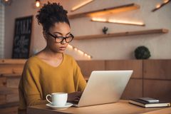 Afro American girl in cafe. Beautiful Afro American girl in casual clothes and glasses is working with a laptop in cafe royalty free stock image