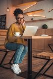 Afro American girl in cafe. Beautiful Afro American girl in casual clothes and glasses is working with a laptop in cafe royalty free stock photography