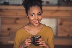 Afro American girl in cafe. Beautiful Afro American girl in casual clothes is holding a cup of coffee, looking at camera and smiling while resting in cafe stock photography