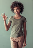 Beautiful Afro American girl. In casual clothes is showing Ok sign, looking at camera and smiling, on gray background Royalty Free Stock Photos