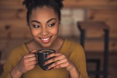 Afro American girl in cafe. Beautiful Afro American girl in casual clothes is smelling coffee and smiling while resting in cafe stock photos