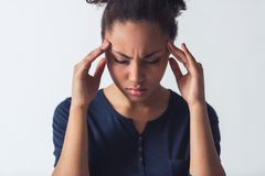 Beautiful Afro-American girl. In casual clothes is touching her temples having headache, isolated on white Royalty Free Stock Image