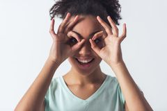 Beautiful Afro-American girl. Cheerful Afro-American girl in casual clothes is gesturing, imitating glasses with her hands and smiling, isolated on white Stock Image