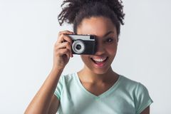 Beautiful Afro-American girl. Cheerful Afro-American girl in casual clothes is taking a photo using a camera and smiling, isolated on white royalty free stock photos