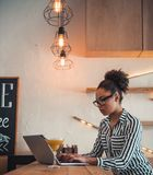 Afro American girl in cafe. Beautiful Afro American girl in smart casual clothes and glasses is working with a laptop in cafe stock photo