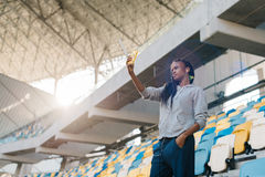 The beautiful afro-american girl is taking selfie via the mobile phone at the backgroud of the seat of the stadium. The royalty free stock image