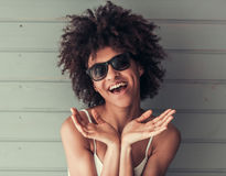 Beautiful Afro American girl. In white top and sun glasses is looking at camera and smiling, on gray wall background Royalty Free Stock Photography