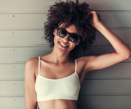 Beautiful Afro American girl. In white top and sun glasses is looking at camera and smiling, on gray wall background Royalty Free Stock Photos