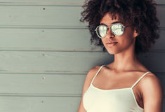 Beautiful Afro American girl. In white top and sun glasses is looking at camera and smiling, on gray wall background Stock Photo