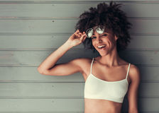 Beautiful Afro American girl. In white top and sun glasses is winking at camera and smiling, on gray wall background Royalty Free Stock Image