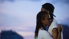 Beautiful afro-american teen girl embracing boy against evening sky, friendship. Stock footage stock footage
