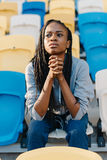 Beautiful afro-american teenager is observing the match on the stadium. Stock Image