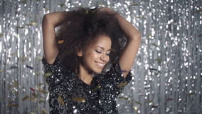 Beautiful afro american woman dancing among golden confetti, slow motion. stock footage