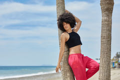 Beautiful afro american woman leaning against palm on beach Stock Photo
