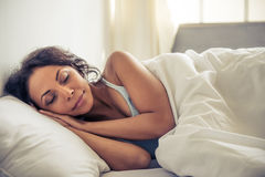 Beautiful Afro American woman. Side view of beautiful young Afro American woman smiling while sleeping in her bed at home Stock Photography