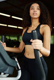 Beautiful afro-american woman spends time in the fitness center. Attractive afro woman with curly hair working out on a stepping machine at gym Royalty Free Stock Photo