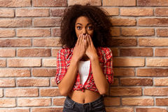 Beautiful Afro-American woman. Young beautiful Afro-American woman posing and covered her mouth while standing against brick wall Stock Photos