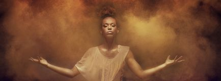Beautiful afro girl dancer over dust. Beautiful african american woman dancer posing over dust. Concept of powerful lady stock photography