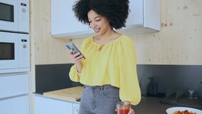 Beautiful afro woman sending messages with her smartphone while drinking tea in the kitchen at coworking place.